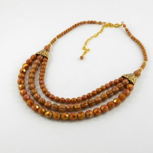 Three strands of glass beads in Opaque Rose Gold Topaz lustre are paired with gold flattened bead-cones with an etched leaf design and the colours echo that of the facades of the Rose City