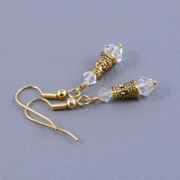 Clear Swarovski Crystals nestle each side of a fancy patterned antiqued gold finished cone to create these delightful earrings.