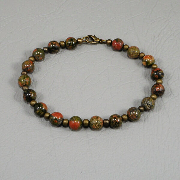 The earthy colours of the natural gemstones in this Unakite bracelet is supported by small round antiqued brass beads. This bracelet measures approx 20cm