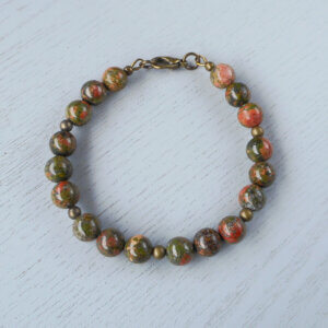 The earthy colours of the natural gemstones in this Unakite bracelet is supported by small round antiqued brass beads