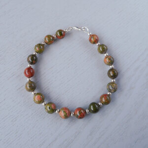The earthy colours of the natural gemstones in this Unakite& Silver bracelet is contrasted by small round shiny silver beads. These beads are not treated.