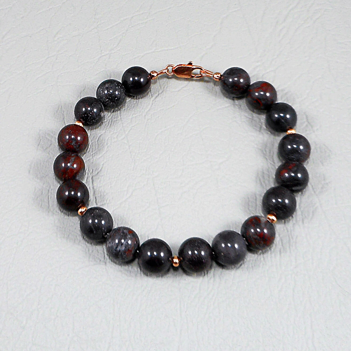 Copper spacers add contrast to the Mustang Jasper with its dark, smoky base and flashes of red. The copper is repeated in the clasp and findings