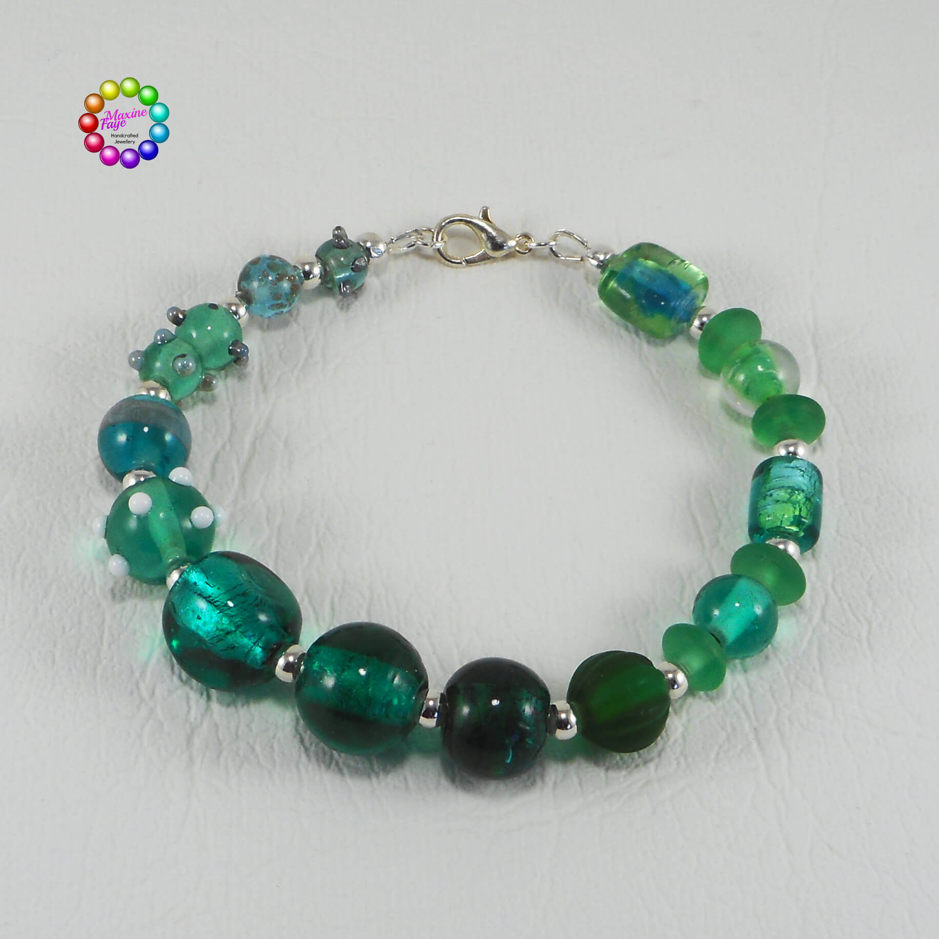 A collection of gorgeous deep teal glass beads are the feature of this beautiful bracelet. Aqua, Emerald and Seafoam greens