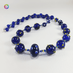 The feature of this necklace is a mix of lamp-work glass beads featuring spots or raised bumps in a combination of white, blue, yellow and pale tea