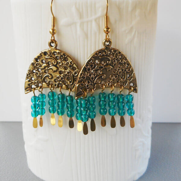 Eucla Statement Earrings A beautiful floral patterned crescent supports six strands of Czech teal pressed glass beads which are threaded onto