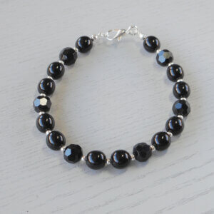 Catherine Black Glass Bracelet Silver spacer beads separate sets of round glass and faceted glass beads to form this stylish bracelet