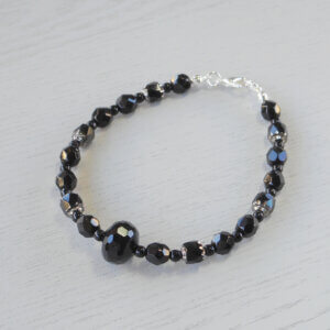 Victoria Faceted Glass Rondel Bracelet Pressed glass beads separate sets of black and silver glass cathedral beads and faceted glass beads to