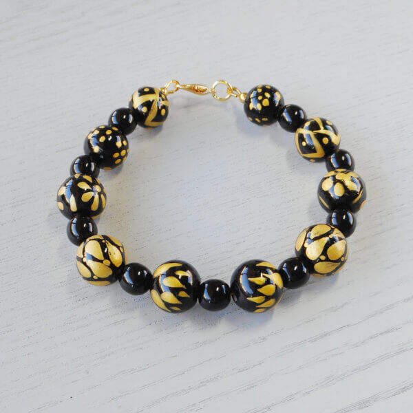 Elegance Hand-Painted Glass Bracelet Alternating sets of plain black and gold and black beads make up this very unusual bracelet.
