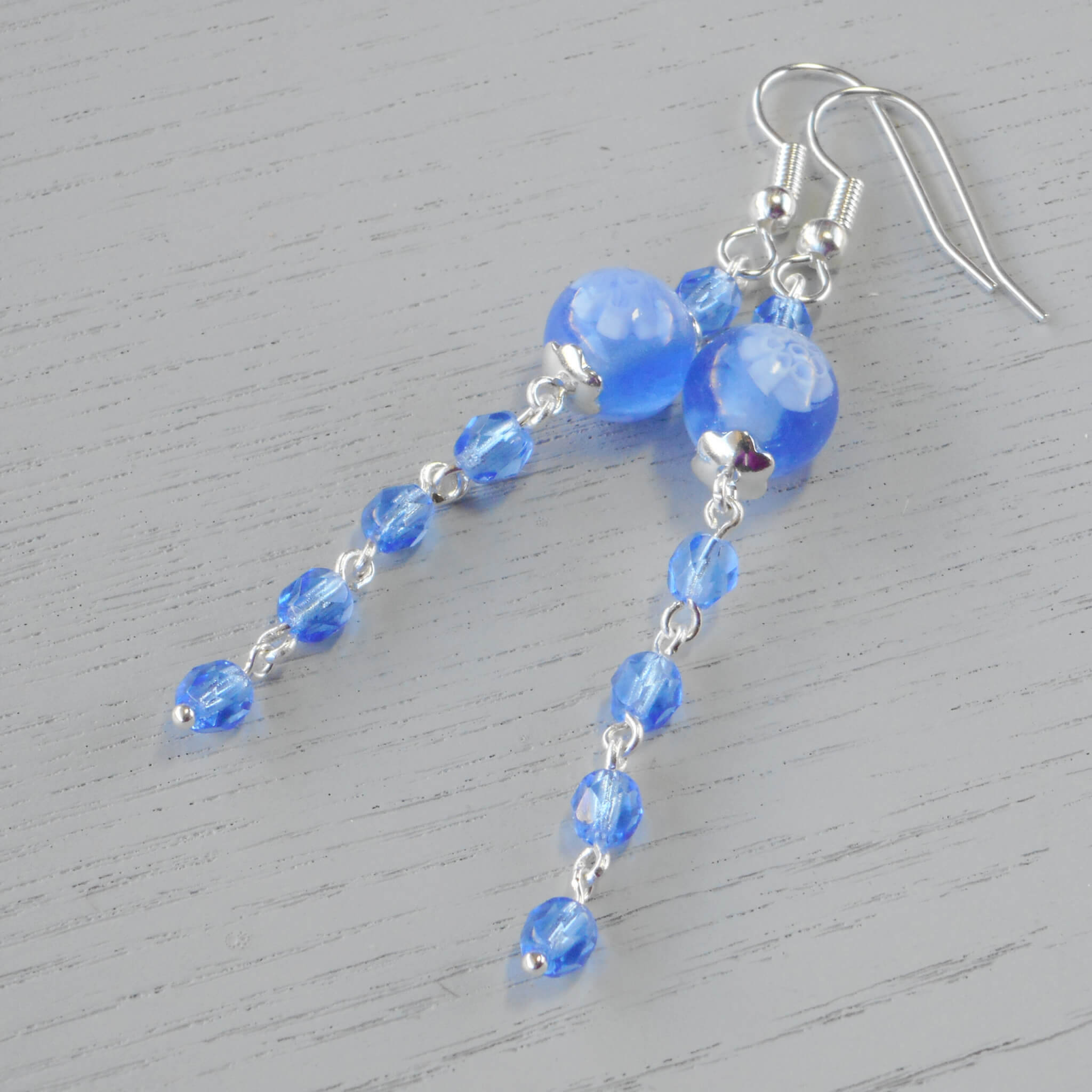 Angelique Millefiori Glass Earrings A beautiful sapphire blue and white Millefiori bead sits between silver scalloped bead caps and is the