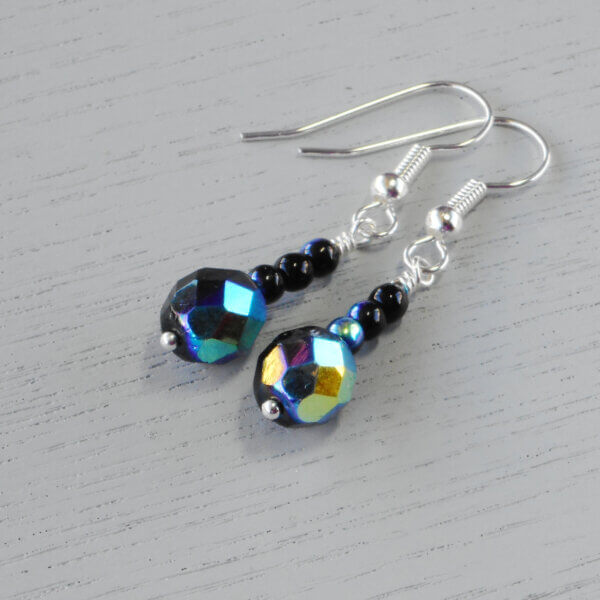 Jessica Jet AB Faceted Glass Earrings Three Czech pressed opaque black glass druk beads sit on top of a 8mm Jet AB faceted round Czech fire polished glass bead to create these stunning earrings.