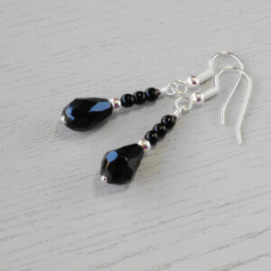 Katherine Faceted Glass Teardrop Earrings A silver spacer bead separates three Czech pressed opaque black glass druk beads from a faceted