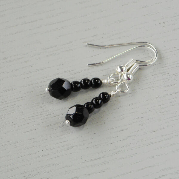 Catherine Black Glass Earrings Three Czech pressed opaque black glass druk beads sit on top of a 6mm faceted round Czech fire polished glass