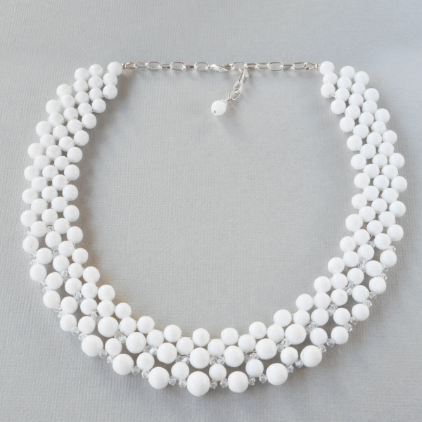 Audrey Glass and Crystal Beaded Necklace This gorgeous, slightly graduated, white glass beaded necklace has a sprinkling of Swarovski