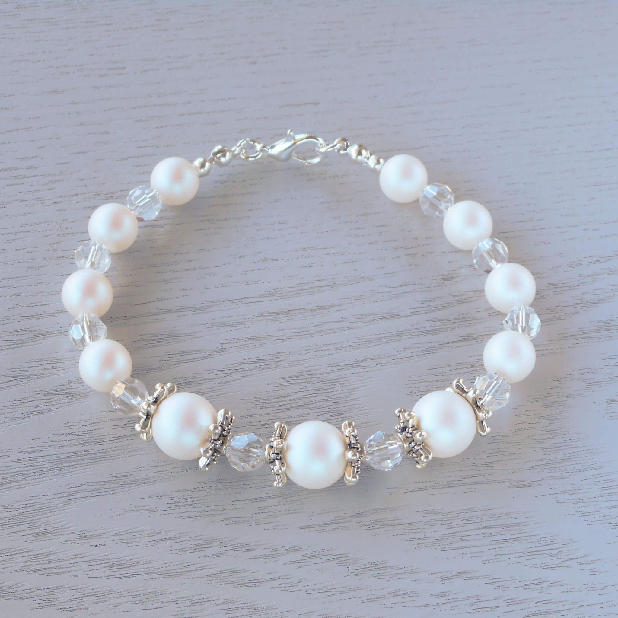 Emilia Glass Crystal & Snowflake Bracelet Ornate snowflake bead-caps separate the frosty Pearlescent White Swarovski pearls and round faceted