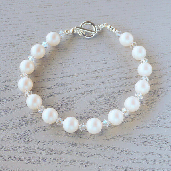 Lisette Glass Crystal Bracelet Pearlescent White Swarovski pearls are separated by Swarovski crystal bicones in Crystal Moonlight