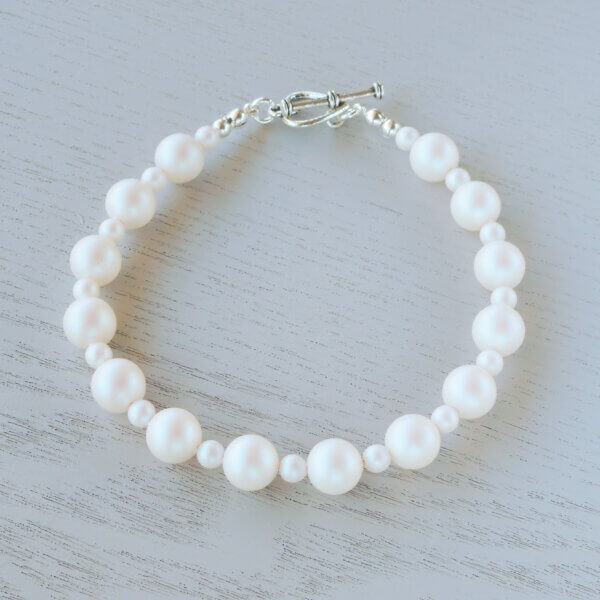 Hazel Glass Crystal Bracelet This gorgeous frosty iridescence strand of Pearlescent White Swarovski glass pearls is finished with a heart toggle